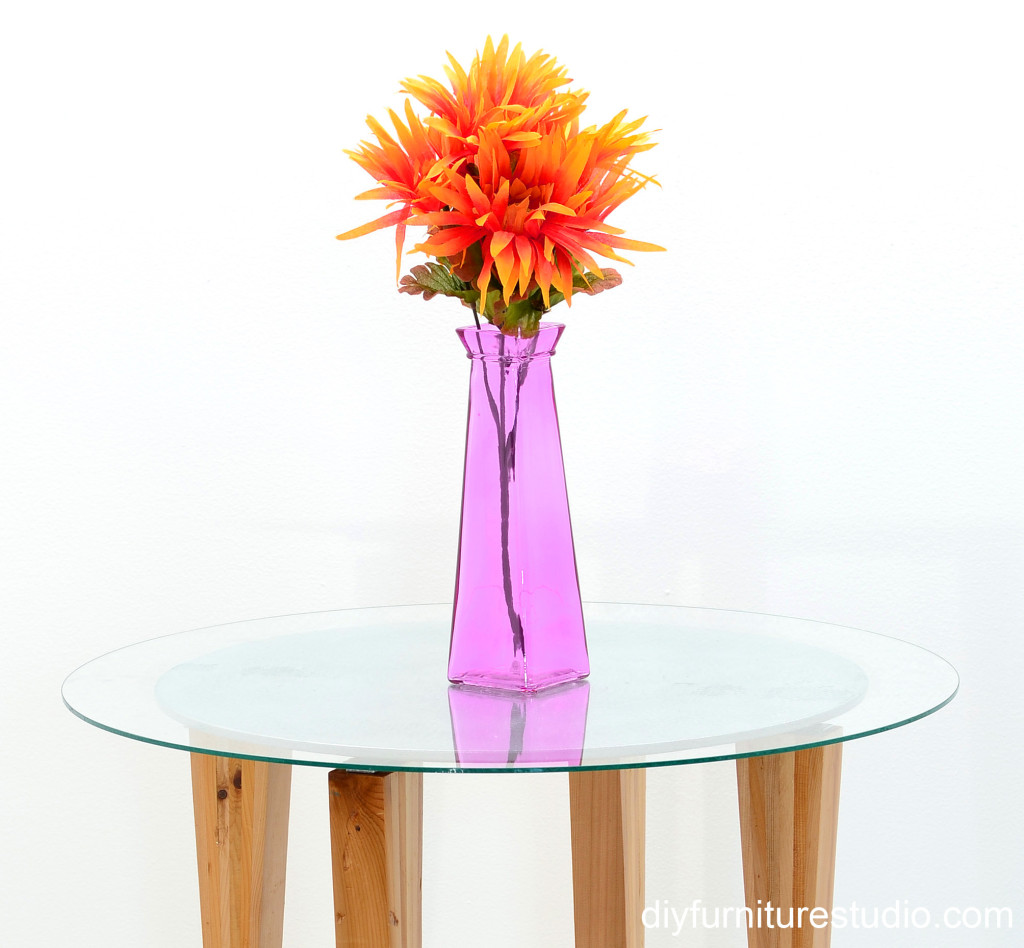 retro style round side table with vase of orange flowers