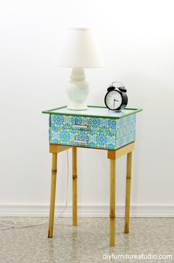 DIY nightstand made of fiberboard drawer unit and bamboo legs.