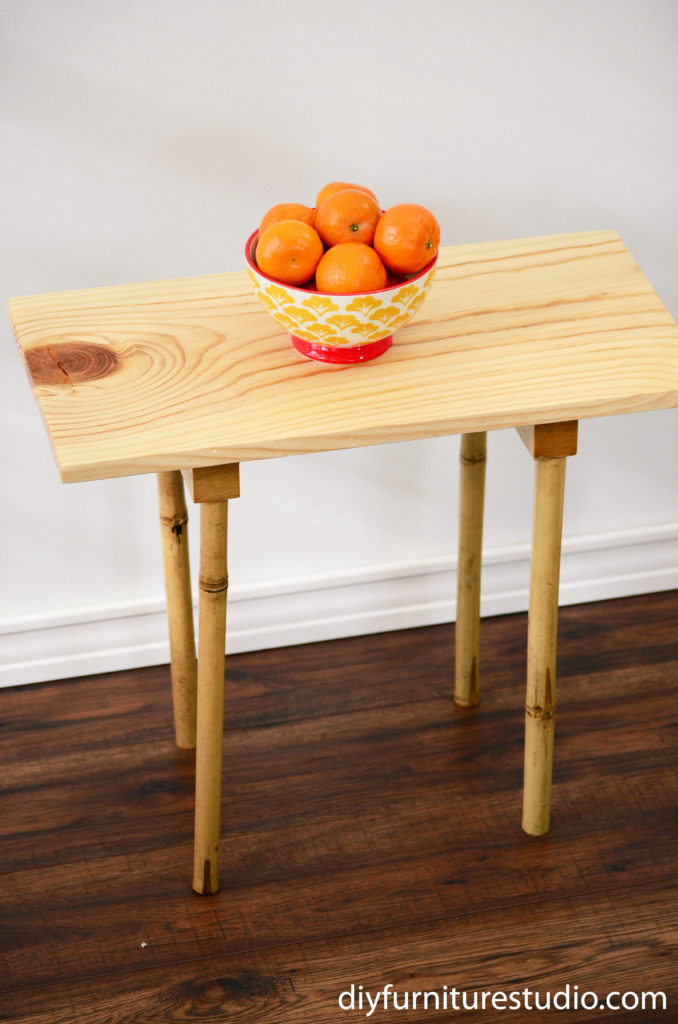 front elevated view of DIY pine board and bamboo leg side table with bowl of oranges