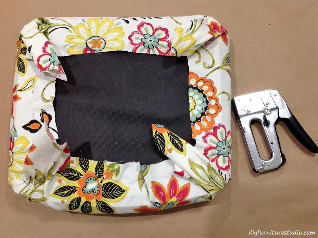 Stapling new fabric to an old cushion for a chair makeover.